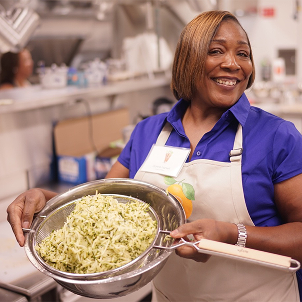 Donna shows off rice in colander